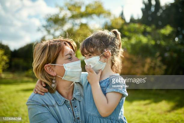 portrait of mother and daughter in protective face masks - prevention stock pictures, royalty-free photos & images