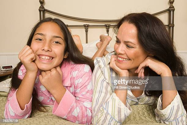 Portrait of mother and daughter lying down on bed