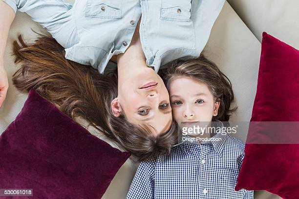 Portrait of mother and daughter lying on floor, smiling