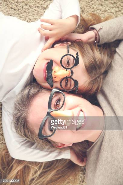 Portrait of mother and daughter lying on the carpet wearing funny glasses with plastic nose