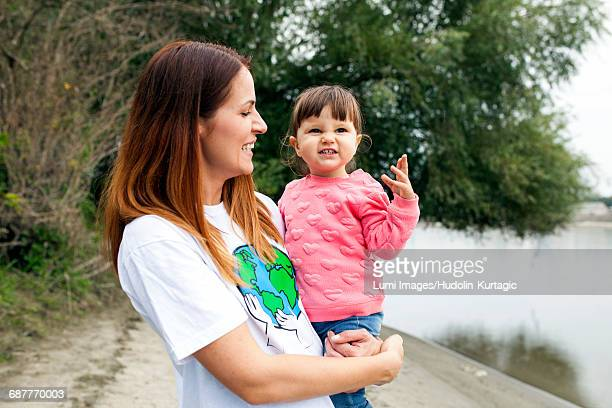 Portrait of mother and daughter on riverbank