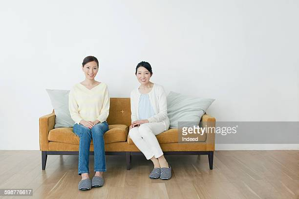 portrait of mother and daughter on sofa - side by side stock photos and pictures