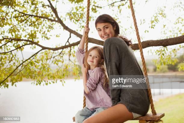 Porträt von Mutter und Tochter auf Schaukel im lakeside