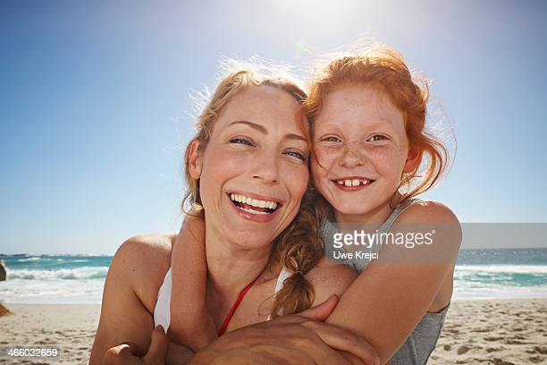 portrait of mother and daughter smiling at beach - sleeveless stock pictures, royalty-free photos & images