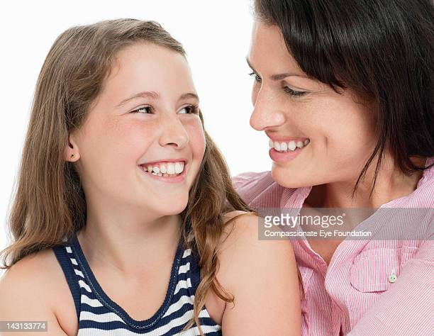 Portrait of mother and daughter, smiling, close up
