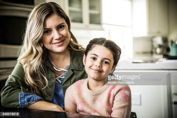 Portrait of mother and daughter (7yrs) smiling, indoors