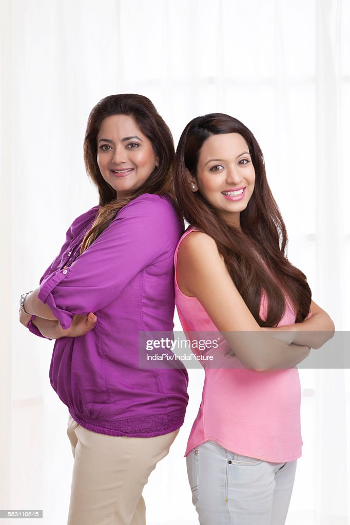 Portrait of mother and daughter standing back to back : Stock Photo