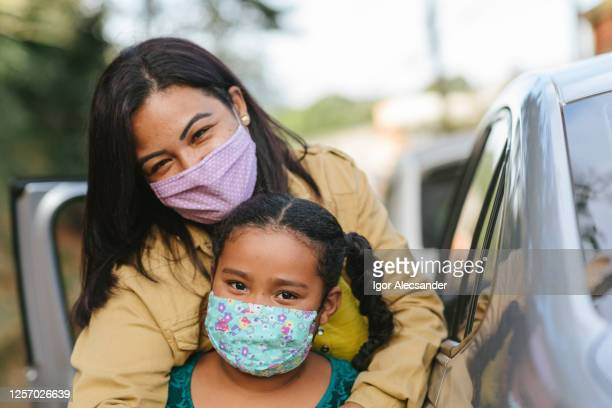 portrait of mother and daughter wearing protective mask on the street - latin american and hispanic ethnicity stock pictures, royalty-free photos & images