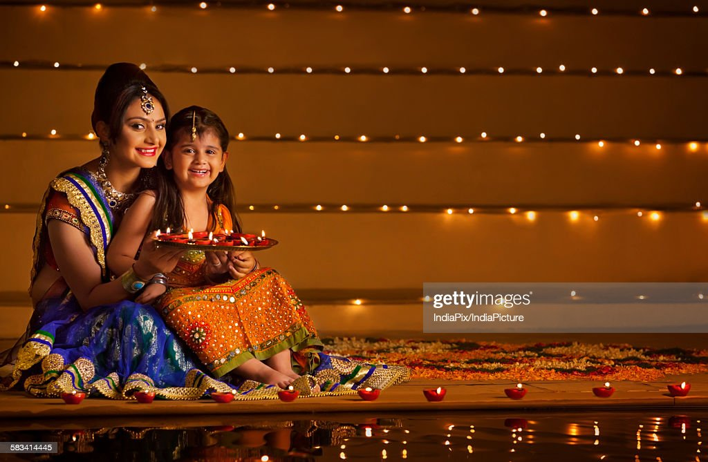 Portrait of mother and daughter with tray of diyas : Stock Photo