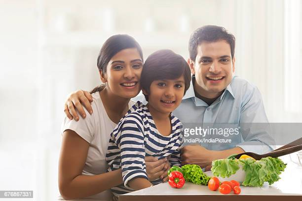 portrait of mother and father with their son sitting together at kitchen table - south asia stock pictures, royalty-free photos & images