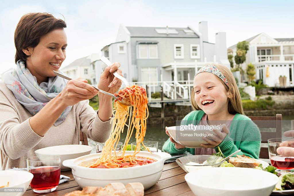 Portrait of mother and girl (8-9), mother serving spaghetti : Stockfoto