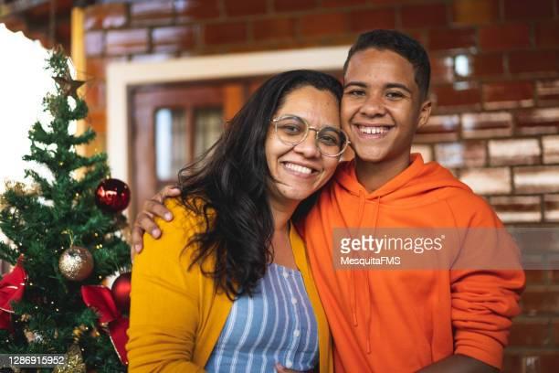 クリスマスを祝う母と息子の肖像画 - オレンジ色のシャツ ストックフォトと画像