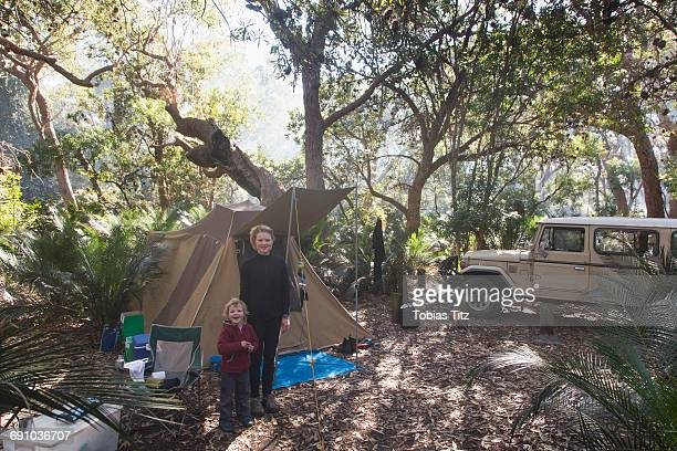 Portrait of mother and son standing outside tent in forest