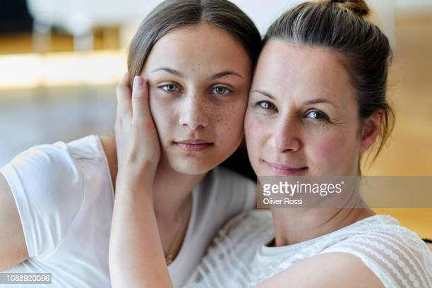 portrait of mother and teenage daughter embracing cheek to cheek at home - brown eyes stock pictures, royalty-free photos & images