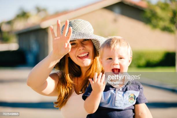 portrait of mother and young son, waving - heshphoto stock pictures, royalty-free photos & images