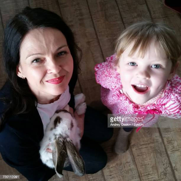 Portrait Of Mother By Daughter With Rabbit On Wooden Floor