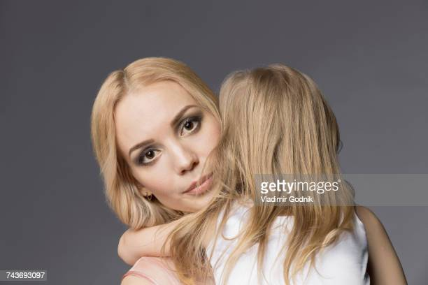 Portrait of mother carrying blond daughter against gray background
