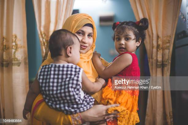 portrait of mother carrying children while standing at home - bangladesh mother stock pictures, royalty-free photos & images