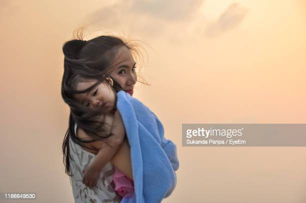 portrait of mother carrying daughter against orange sky - towel stock pictures, royalty-free photos & images