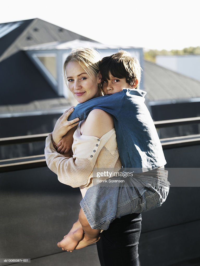 Portrait of mother carrying son (8-9) piggy back at balcony : Foto stock
