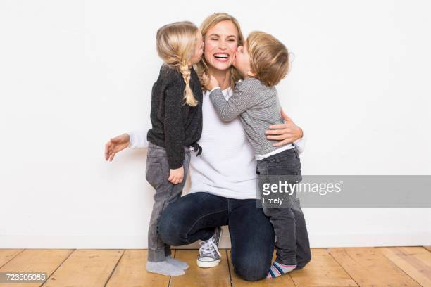 portrait of mother, crouching, hugging son and daughter - family with two children stock photos and pictures
