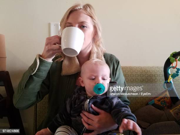 portrait of mother drinking coffee while carrying son at home - mom sits on sons lap stock pictures, royalty-free photos & images