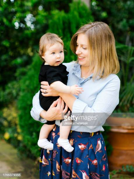portrait of mother holding baby daughter (12-17 months) - 12 17 months stock pictures, royalty-free photos & images