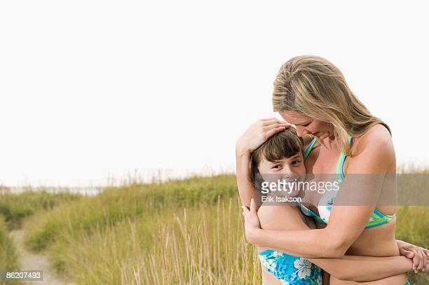 Portrait of mother hugging daughter on beach