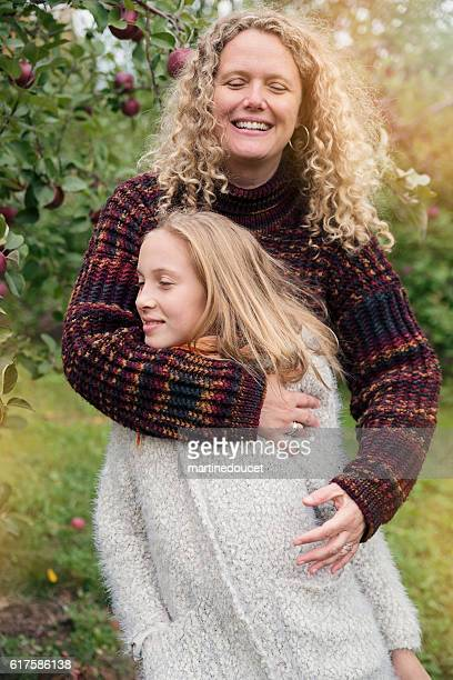 Portrait of mother hugging teenage daughter in orchard.