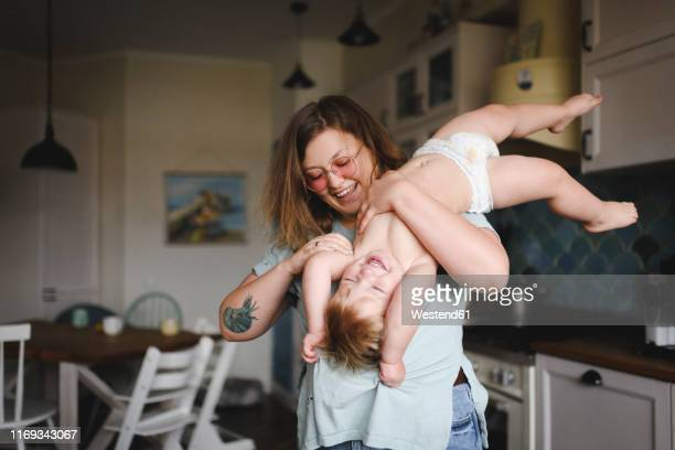 portrait of mother playing with her little son in the kitchen - diaper kids stock pictures, royalty-free photos & images