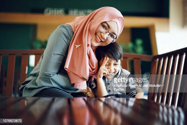 portrait of mother smiling while sitting with son at table - muslim mother stock pictures, royalty-free photos & images