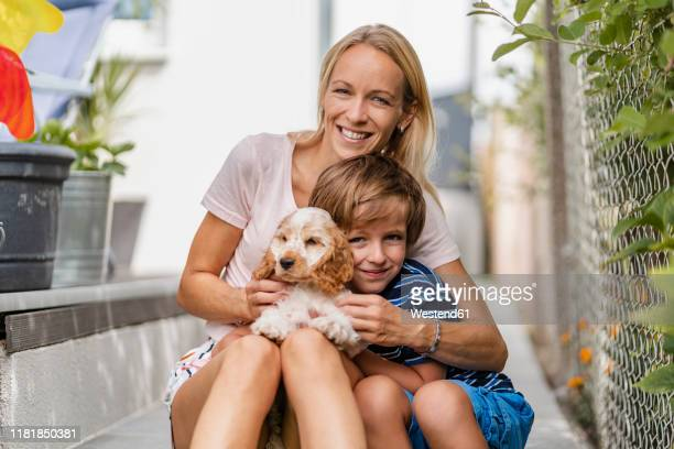 portrait of mother snd son cuddling with cute dog puppy - one animal stock pictures, royalty-free photos & images