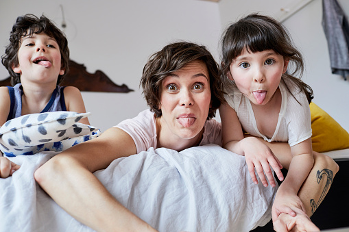 Portrait of mother, son and daughter, lying on bed, poking tongue out - gettyimageskorea