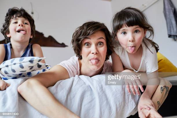 Portrait of mother, son and daughter, lying on bed, poking tongue out