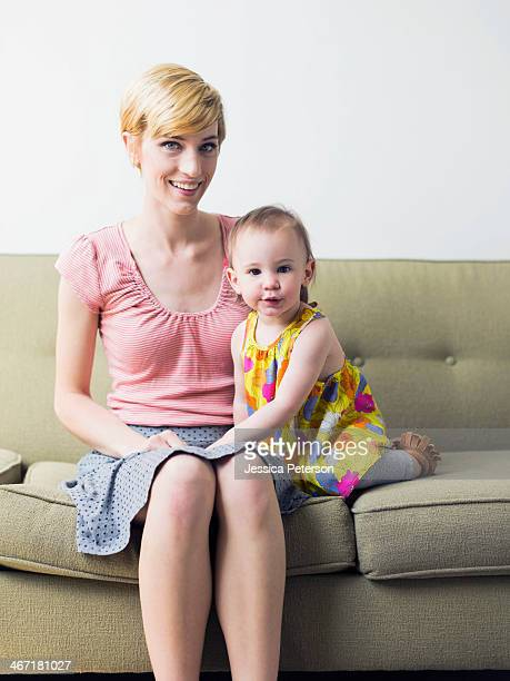 Portrait of mother with daughter (12-17 months) sitting on sofa