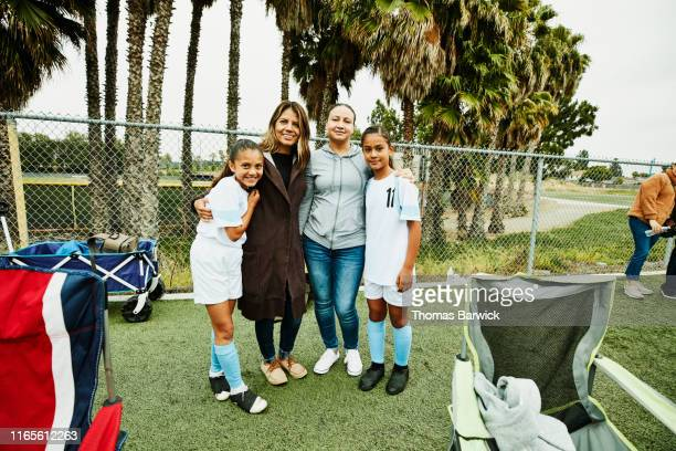 Portrait of mothers embracing daughters on sidelines after soccer game