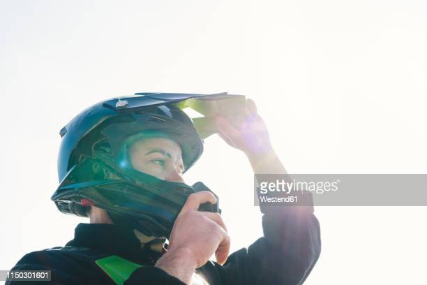 portrait of motocross driver putting on helmet at sunset - sports helmet stock pictures, royalty-free photos & images