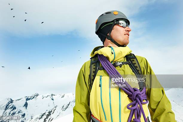 Portrait of mountaineer on snow-covered mountain looking away