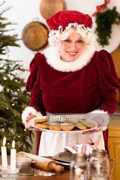 portrait of mrs. claus holding fresh gingerbread cookies - weihnachtsfrau stock-fotos und bilder