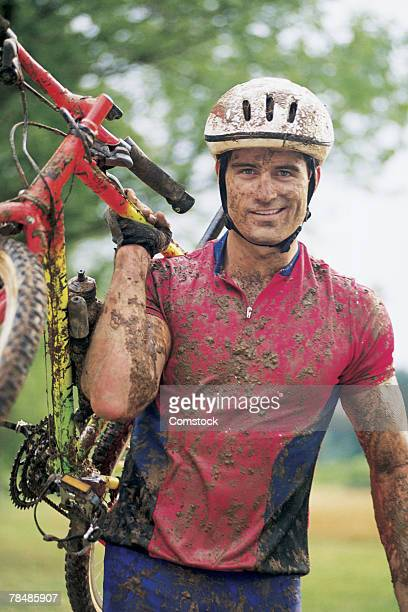Portrait of mud-splattered man with mountain bike