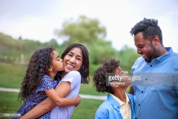 portret van multicultureel gemengd ras multi-etnische familie die bij openbaar park koestert - kroeshaar stockfoto's en -beelden