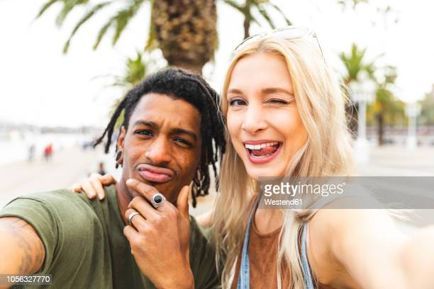 portrait of multicultural young couple taking selfie - self portrait photography stock pictures, royalty-free photos & images