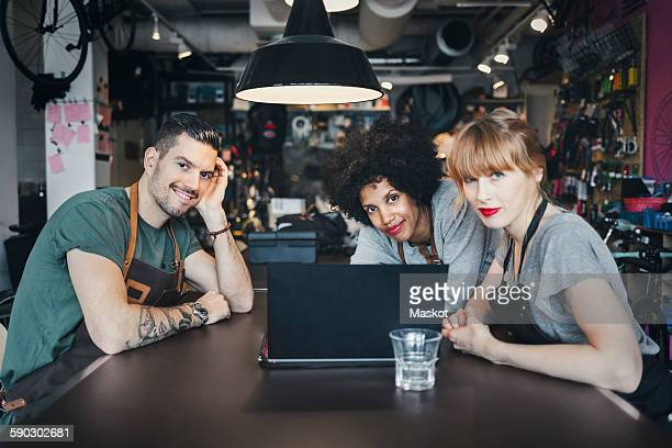 Portrait of multi-ethnic mechanics with laptop at table