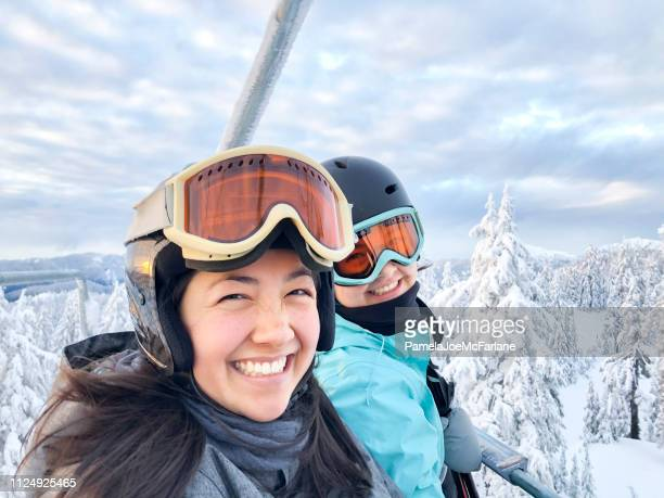 portrait of multi-ethnic sisters riding chairlift, ski runs in background - vancouver canada stock pictures, royalty-free photos & images