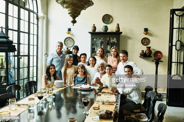 Portrait of multigenerational family gathered at dining room table for birthday dinner