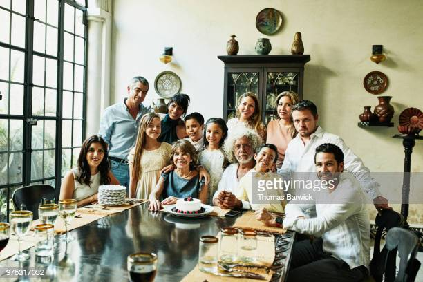 Portrait of multigenerational family gathered in dining room during celebration dinner