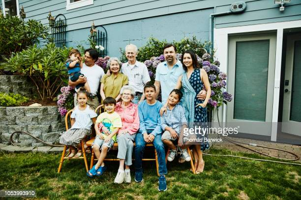 portrait of multigenerational family in backyard garden on summer evening - 90 plus years stock pictures, royalty-free photos & images