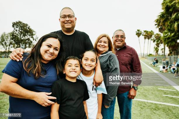 portrait of multigenerational family on field after daughters soccer game - latino américain photos et images de collection