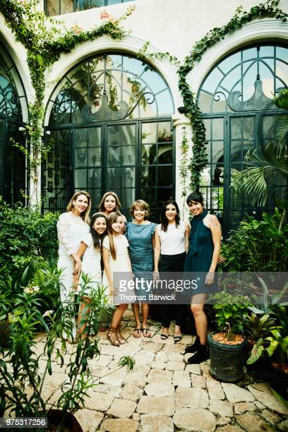 Portrait of multigenerational female family members standing in garden courtyard after family dinner party