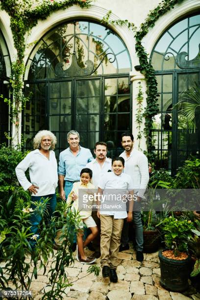 Portrait of multigenerational male family members standing in garden courtyard after family dinner party